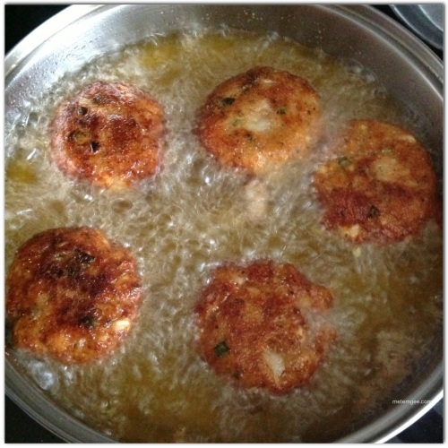 Add about 3 cups of oil to a frying pan on medium heat. When the oil is hot, add salt fish cakes.  Cook on one side until golden brown (about 4 minutes), then flip and cook on the other side until golden brown.