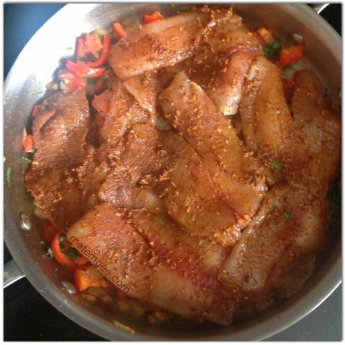Add seasoned tilapia to the top of the cooked seasoning. Reduce heat, cover and let steam for about 5 minutes.